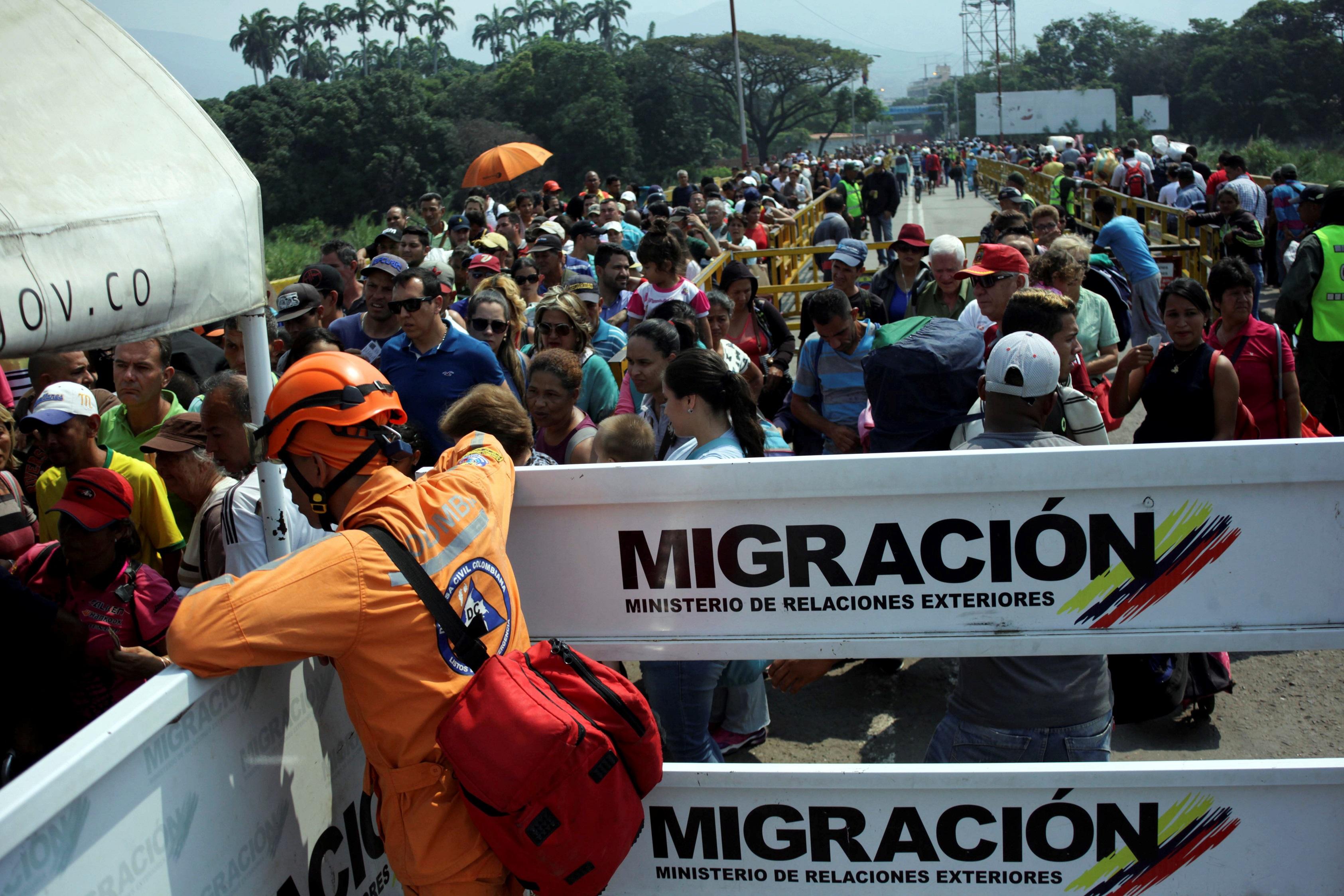 Тем временем венесуэльцы бегут в Колумбию по мосту Симона Боливара.