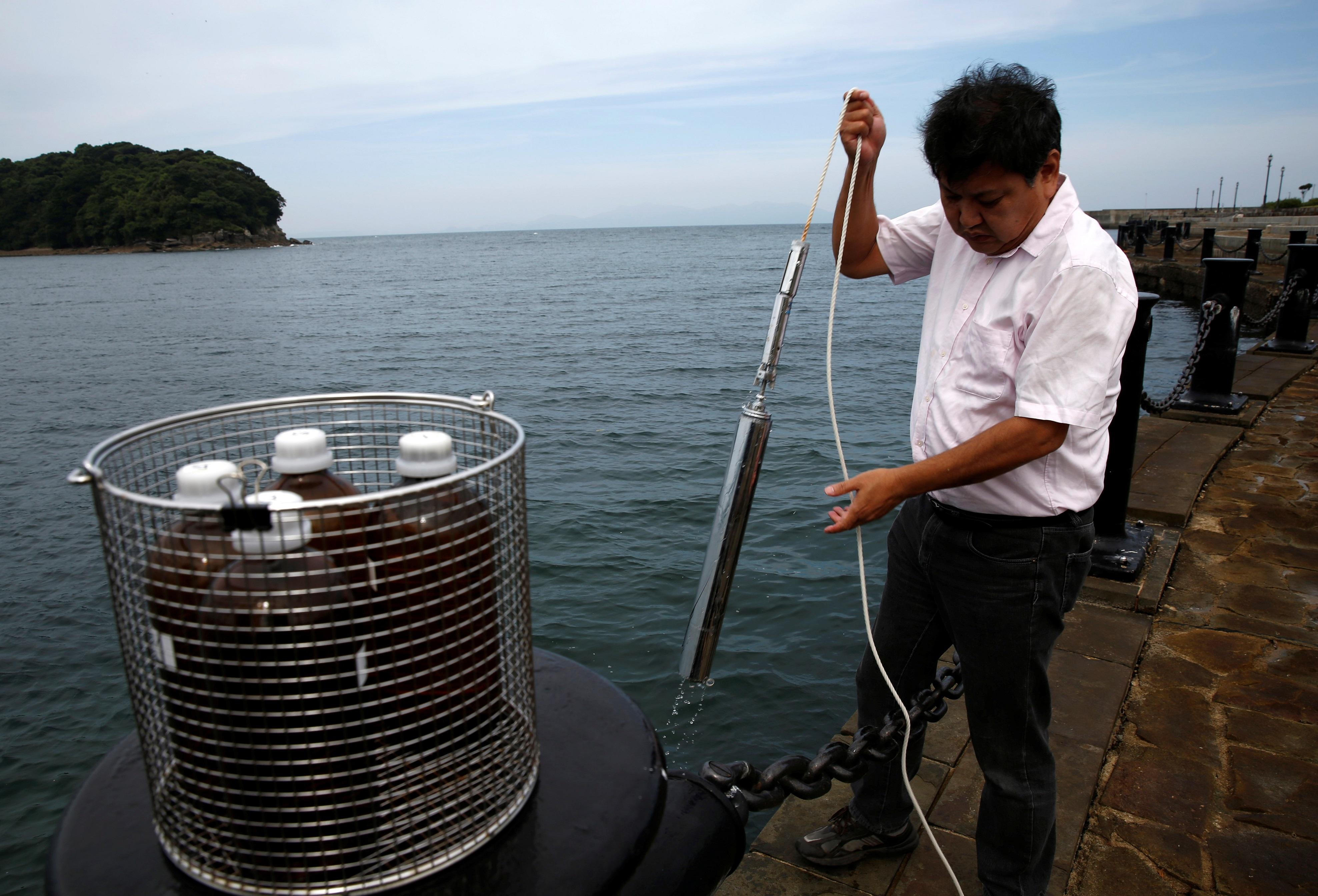 Инженер из Национального института Минамата собирает образцы воды из залива